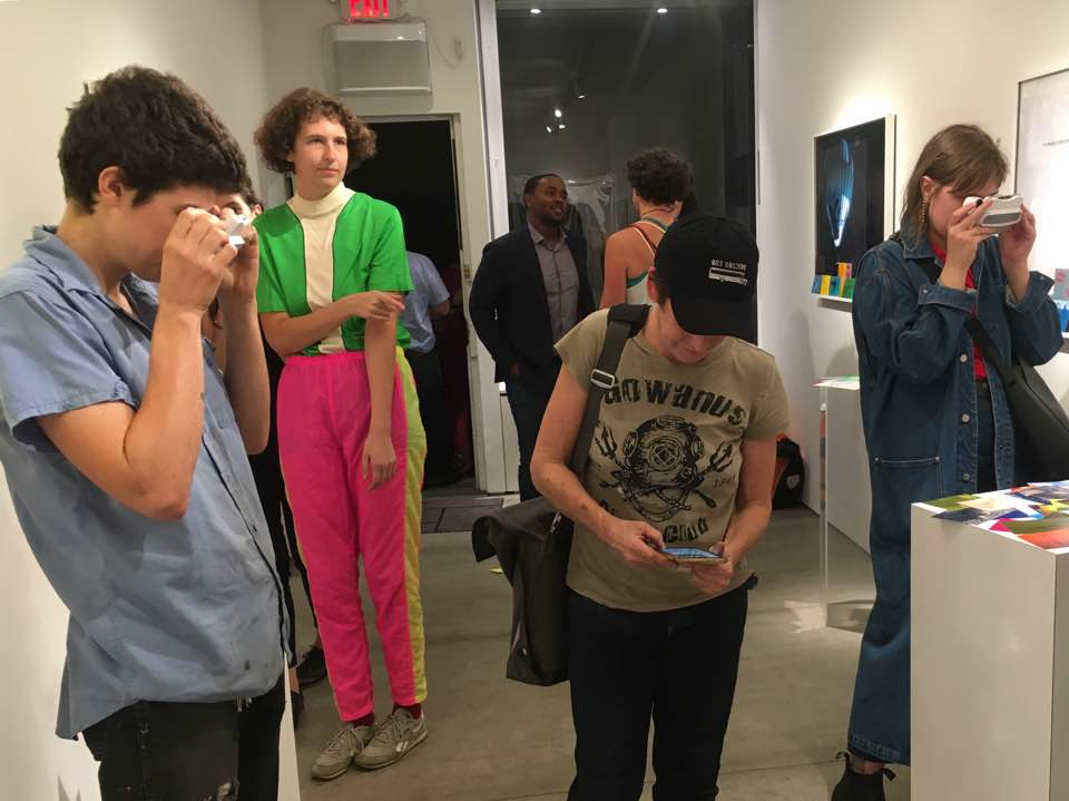 This is gallery shot at Capsule NYC shows visitors reading the 3d viewfinder essays.