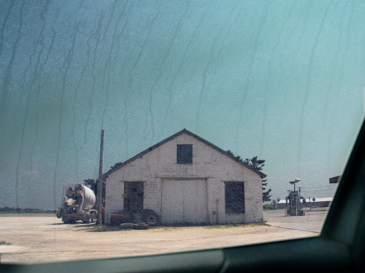 Image of white building with cement truck next to it shot through a streaky car window.