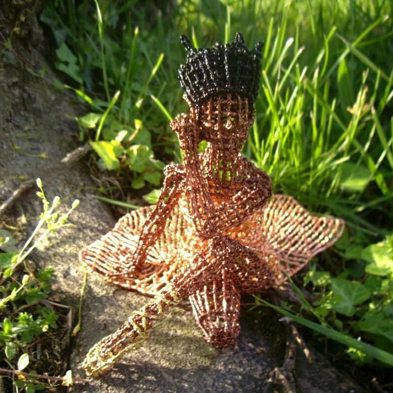 Wire ballerina seated in nature