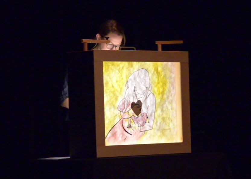 A drawing seen with light projected behind it of the moment my child is born and placed in my arms.