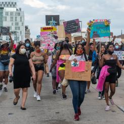 Black Womyn holding signs while marching up north avenue demanding justice