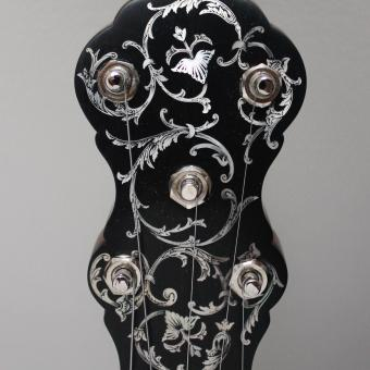 Peghead of banjo with mother of pearl inlay and engraving.