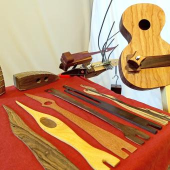 Display of daxophone tongues (foreground), daxes (left), daxulele (right), desk mounted daxophone with kalimba tongue (center), and tripod daxophone (center, rear).