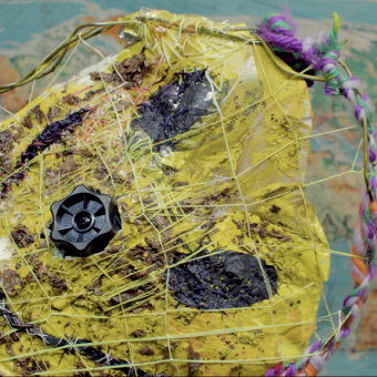 Film still of a toxic yellow smiley face mask worn by a human to convey the terror of forced happiness