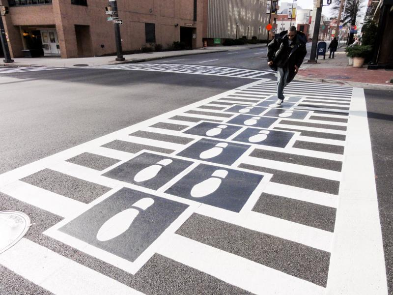 Hopscotch Crosswalk Colossus - business man jumping shoe prints
