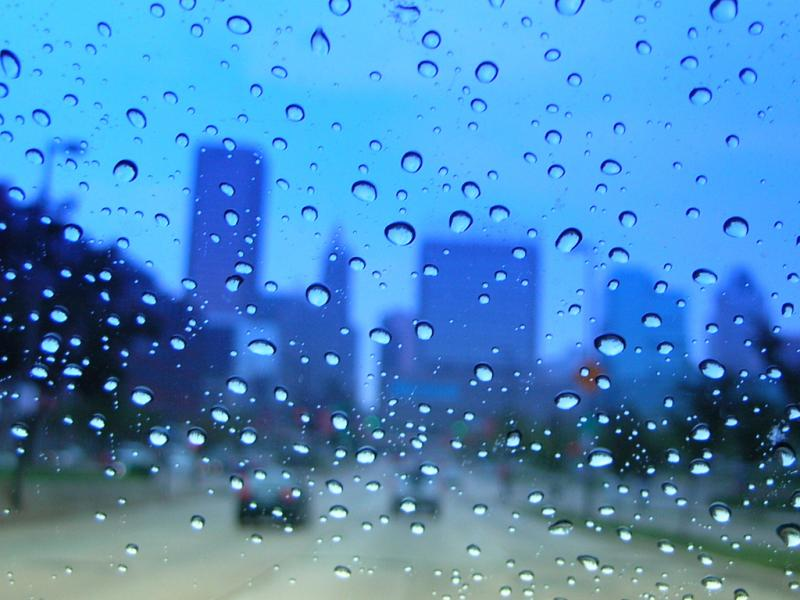 downtown through a wet blue car window