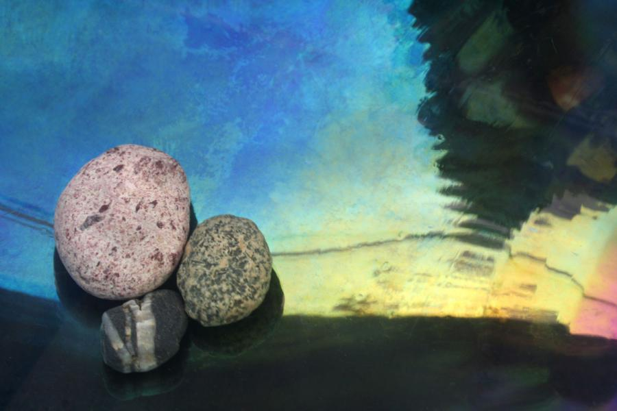 three stones on a dark field with blue sky