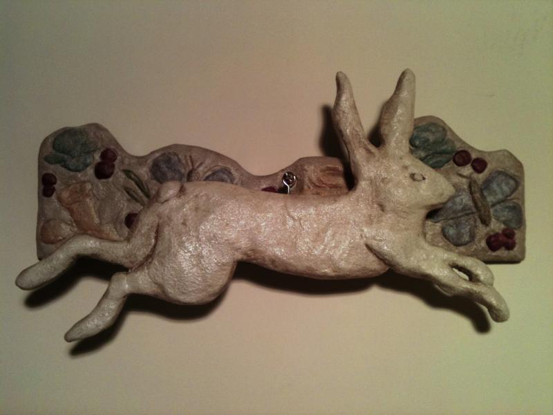 rabbit swinging concrete wall sculpture