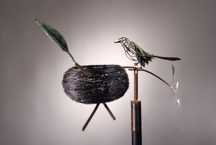 """wood thrush.... a nest with eggs... leaves balanced on a ne72"""" long steel branch rotates 360 degrees.... bobbs up and down... supported by a stylized shovel. ideogram: transparent qualities of woodland birds and animals, individual leaf, domed-shaped"""