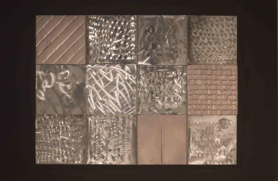 Chicago: dumpster diving at the building site finding aluminum and stainless steel scrap.  A very cold January day. 12 aluminum and stainless steel patches, ground, woven and plaited. quilted with stainless steel strip