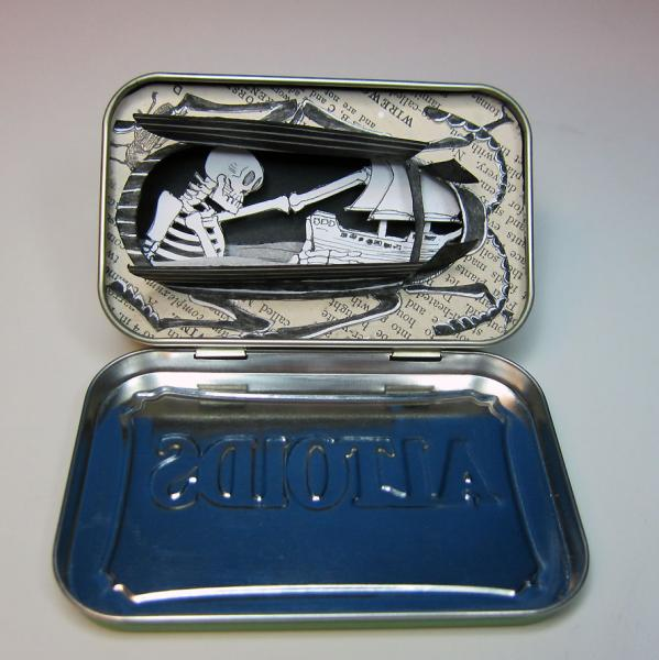 A cut paper Death Watch Beetle in an altoids tin, wings spead to reveal a giant skeleton  launching a ship across the dead sea.