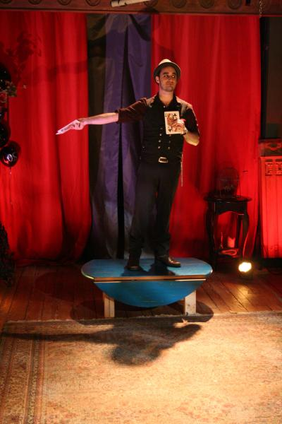 Magician stands center stage with large cards.