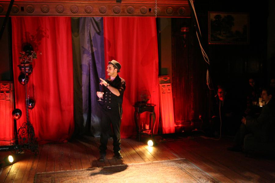 Magician stands center stage in front of red curtains.