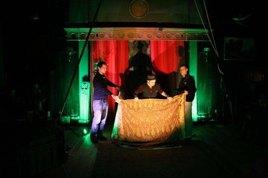Magician stands with volunteers and a large curtain.
