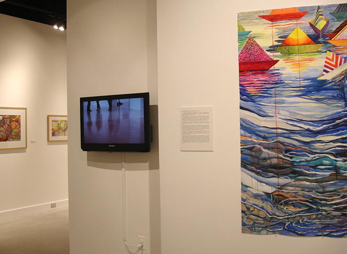 The video, Reflection, is placed in the gallery among Diana Marta's paintings at Towson University in June of 2014