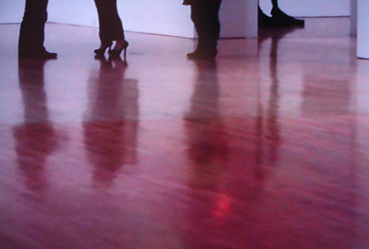 The feet on the shiny museum floor give viewers a sense of live feed, which emphasizes the timeless quality of museum viewing.