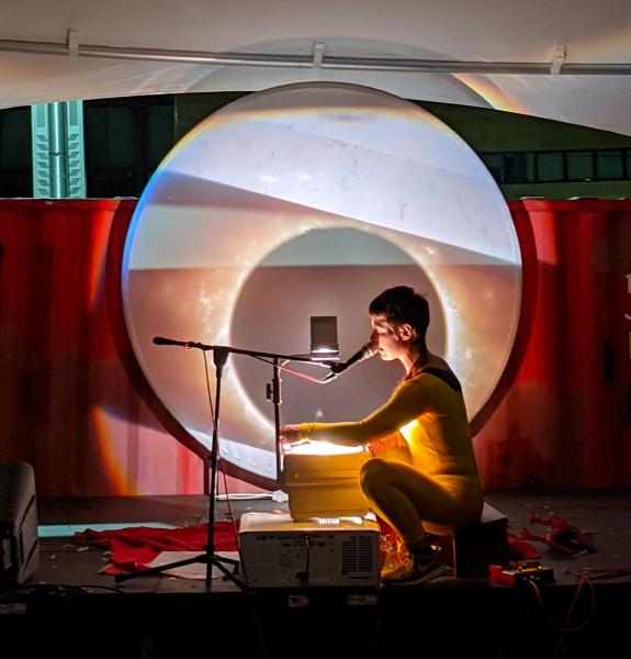 Rae Red singing with an overhead projector in front of an image of the sun.