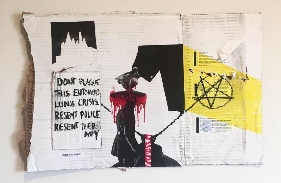 A photo of a mixed media artwork against a white wall.