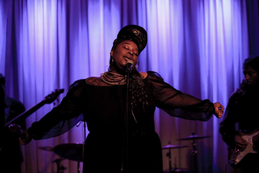 Black Womyn with her arms stretched performing on stage. The background is purple and the Womyn has on a long black dress and a black and gold headdress