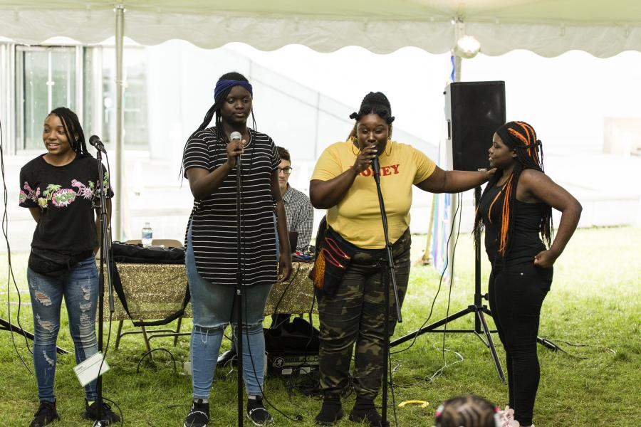 3 young black girls and 1 adult standing on stage with mic preparing to perform.