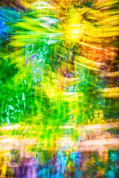An abstract photograph created by camera movement evoking light glowing through stained glass or the transparency of layered dyes in batik.