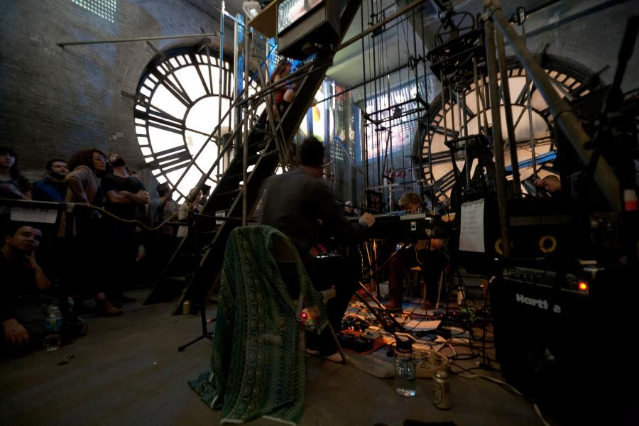 Peals performing inside the Bromo Seltzer Tower clock room with projections by Zoe Friedman