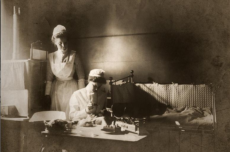 Two women administer drops to a newborn's eyes to prevent blindness, c. 1905.