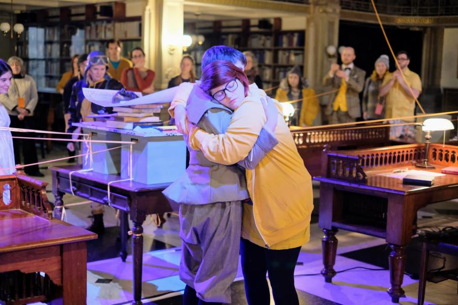 See Also - performers Jess Rassp and Emily Hall embrace during the culmination of the show, surrounded by other performers and audience members in the library