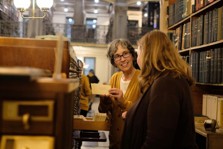 "performer Ursula Marcum and audience member at the card catalog in ""See Also"""