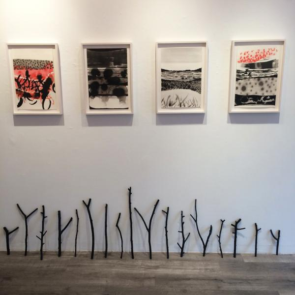 Installation view of framed drawings by Magnolia Laurie and black stick sculptures leaning against a wall.