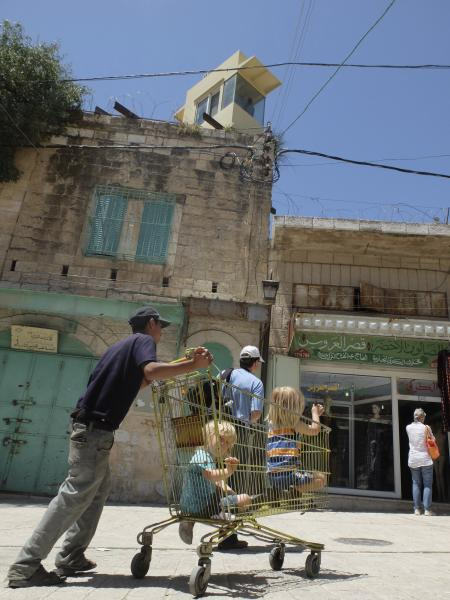 boys in shopping cart in Palestine with Israeli guard above