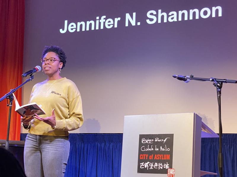 a photograph of Jennifer N. Shannon on stage, reading at City of Asylum in Pittsburgh, PA.