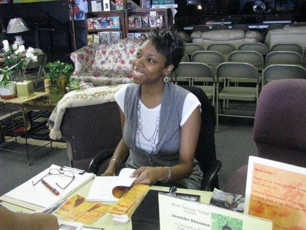 Jennifer N. Shannon smiling while sitting with a book ready to sign