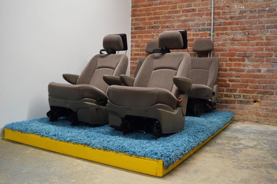 four car seats on a platform with blue shag carpeting