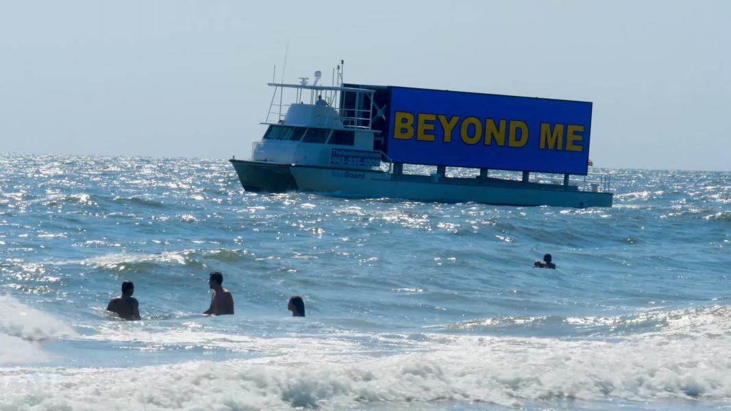 boat in ocean with LED screen that reads 'Beyond Me'