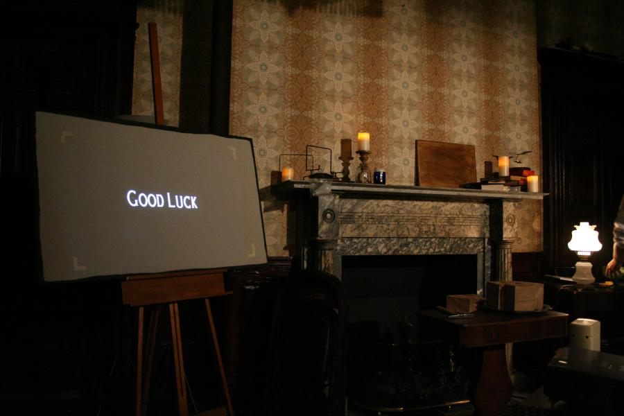 "Fireplace with candles, with screen reading ""GOOD LUCK"""