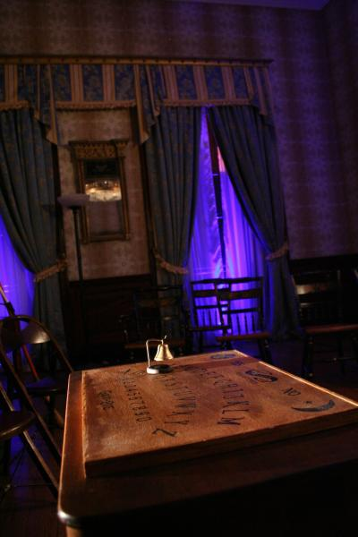 A purple light on curtains in the background, Ouija board and bell in the foreground.