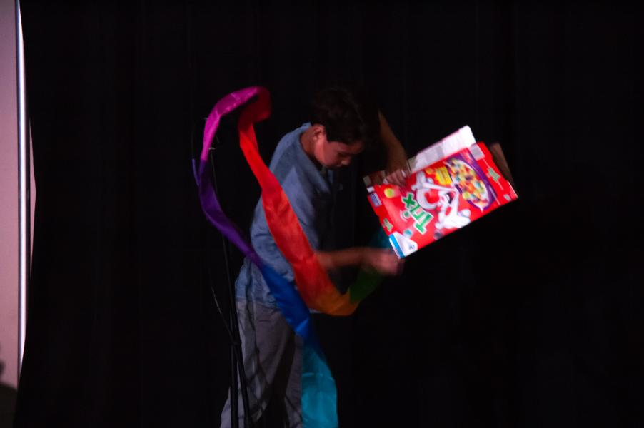 Student magician performs a silk effect with a cereal box.