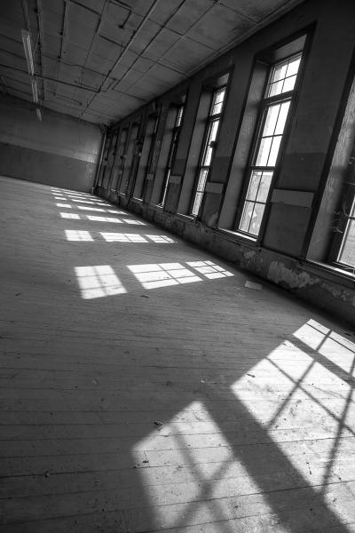 Patterns of sunlit windows fall onto the dusty floor of an empty industrial building in east Baltimore.
