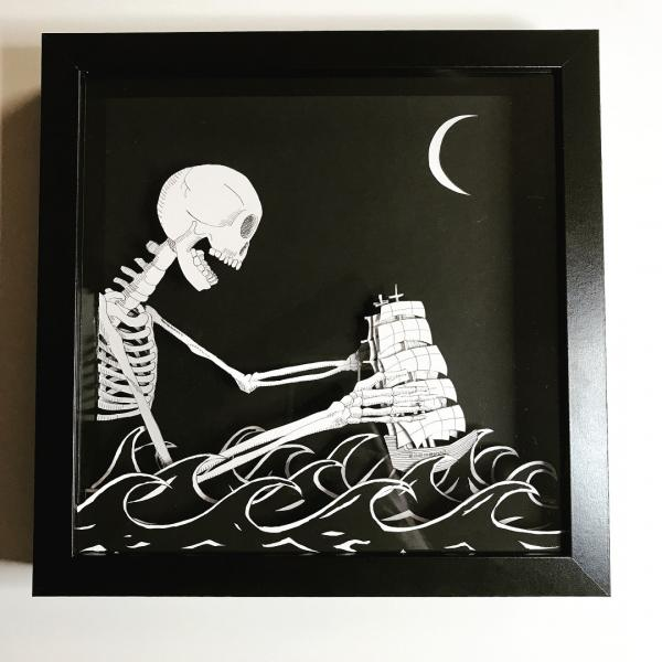 Shadow box with a Giant Skeleton pushing a boat in the sea