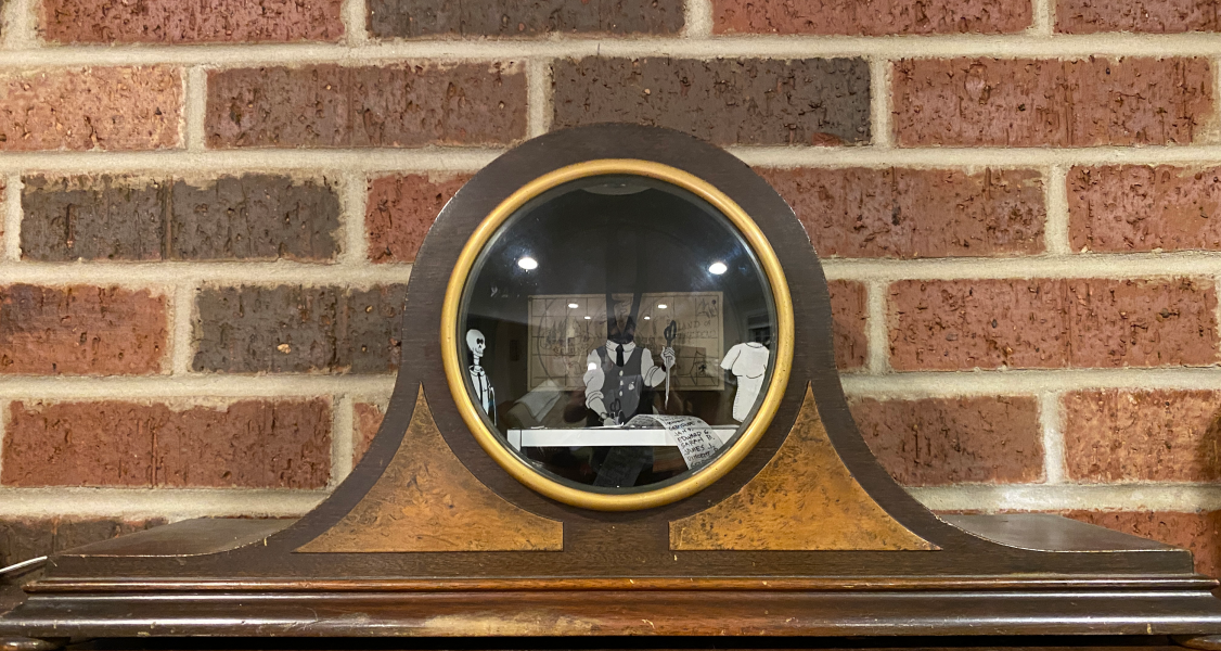 Diorama in a mantle clock case sitting on a mantle by a brick wall