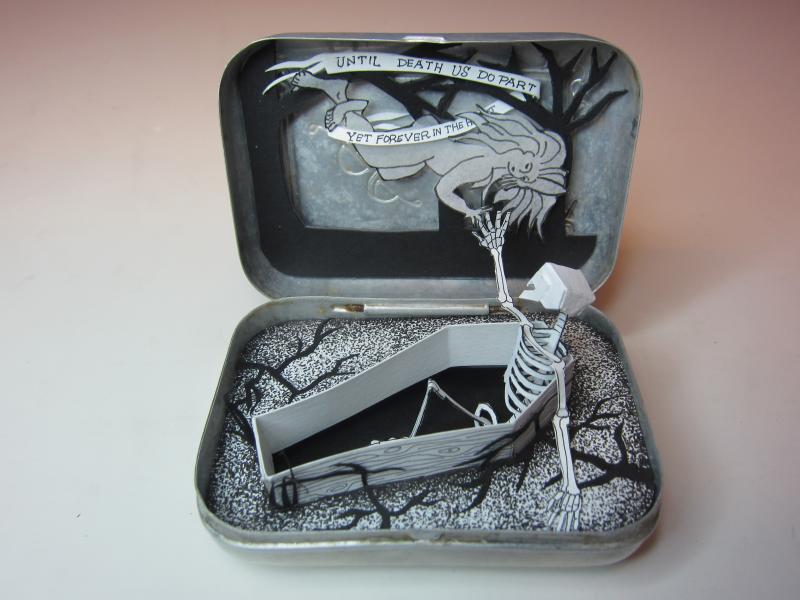 Always diorama, cut paper skeleton in a vintage soap tin.