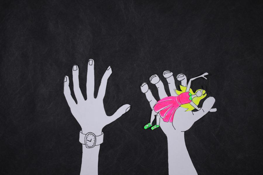Giant hands holding the figure of a girl