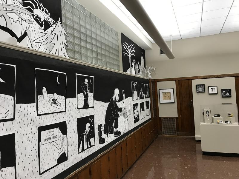 View of the gallery, with a giant 20' x 4' comic on the wall spaning the length of the room.