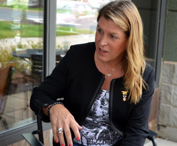 Image of Kristen Beck in a black sports coat, talking while gesturing with her hand