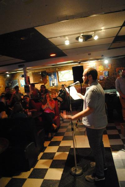 A man reads into a microphone before a crowd in a bar