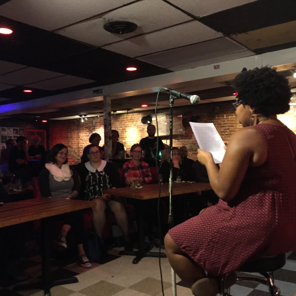 A woman is seated in front of a mic, reading from a paper in front of a crowd in a bar